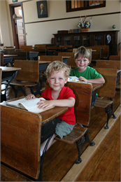 Two students sit in 1930s style school desks.