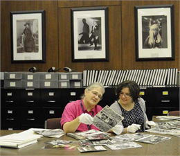A researcher and staff member look at photos with white gloves in the Archives reading room.