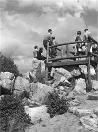 A view from below of a lookout area filled with visitors on Rib Mountain.