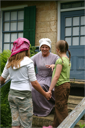 A tour guide in costume talks with two students.