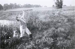 Woman posing in field. Photo was later made into a postcard by adding oversized frogs.